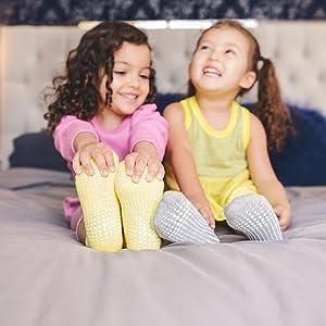 due bambine sul letto in calzini aderenti grigi gialli che ridono sorridenti e confortevoli