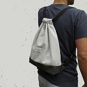 Uomo con un peso grigio chiaro sulla schiena di fronte a un muro