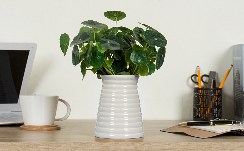 Decorative white round vase with ribbed edge featuring greenery on a desk
