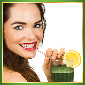 Smiling beautiful woman drinking Ultimate Organic Green Superfood from a glass with a straw