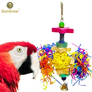 A cute red bird is playing with the Shredder Bird Toy bu SunGrow