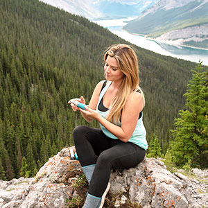 Woman dispensing Asara Advanced Face Cream into hand while sitting atop a mountain with stream below