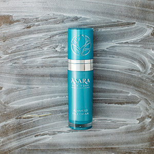 Asara Advanced Face Cream bottle placed flat on surface with cream spread around on surface.