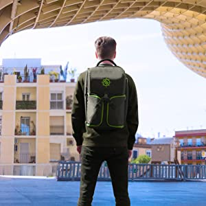 Urban landscape with man wearing backpack facing away from camera