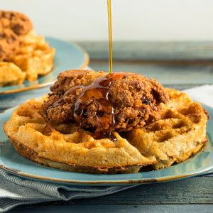 Syrup being Poured on Chicken and Waffles