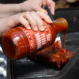 BBQ Sauce poured on steak for grilling