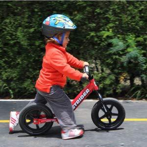 Toddler riding a red Strider Balance Bike 12 Sport
