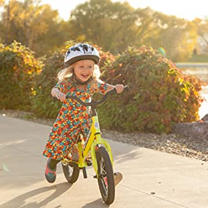 Young girl riding her yellow Strider 14x balance bike without pedals