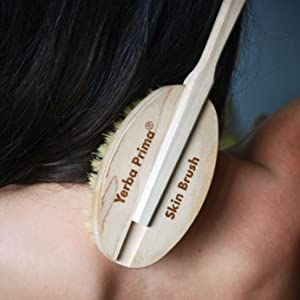 a black haired woman scrubbing her back with a wooden tampico skin brush to exfoliate her skin