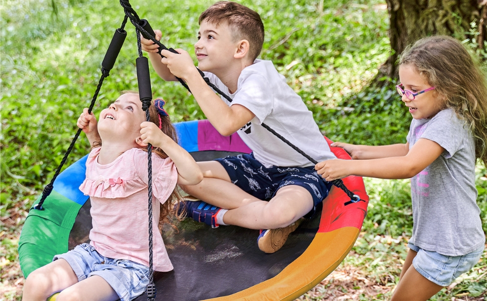 3 children on a rainbow colored tree swing