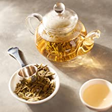 A teapot that is steeping a cup of white tea
