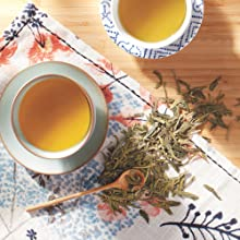 a freshly brewed cup of white tea with tea leaves next to it