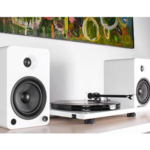 Kanto Matte White YU6 powered bookshelf speakers next to white turntable
