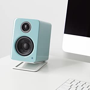 Kanto YU2 gloss teal on white desktop stand next to iMac and keyboard
