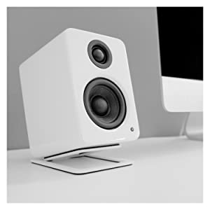 White YU2 speakers atop white speaker stand next to iMac