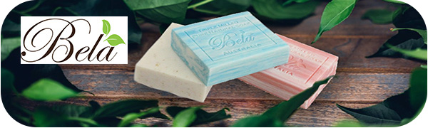Three Bela soap bars on wooden planks with leafy greenery and Bela logo.