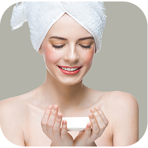 Woman with hair in towel wrap holding soap with her eyes closed.
