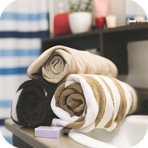 Three rolled towels with bar of soap on sink