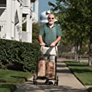man walking home with cart and groceries