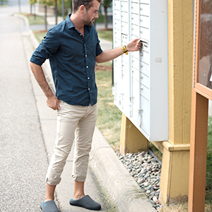 Man wearing slippers with an outdoor-ready rubber bottom, checking his mailbox outside the house.