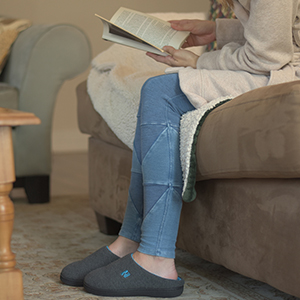Woman relaxing in a pair of slippers at home. She sits on the living room couch reading a book.