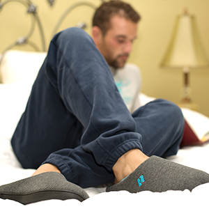 Man sitting on bed in the bedroom, reading a book and relaxing in a pair of RockDove slippers.