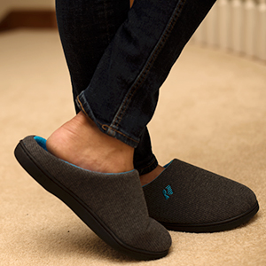 Man wearing RockDove slippers inside the house on carpet, focus on his feet.