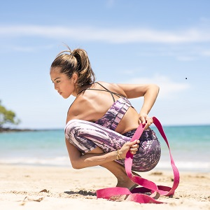 Girl using yoga strap in yoga pose on