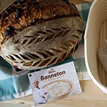 baked loaf on table with banneton bread proofing basket and bread bosess hangtag on top of cloth
