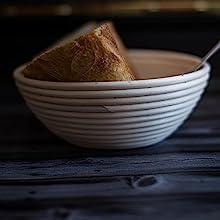 Baked sourdough bread placed inside banneton bread proofing basket