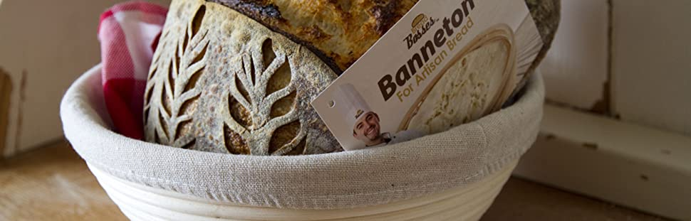 banneton bread proofing basket set on the table with baked sourdough bread placed in bread basket