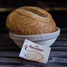 Baked sourdough bread placed inside banneton bread proofing basket with cloth liner on bread basket