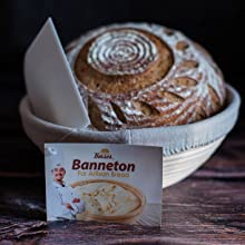 banneton bread proofing basket set on table with cloth liner and dough scraper