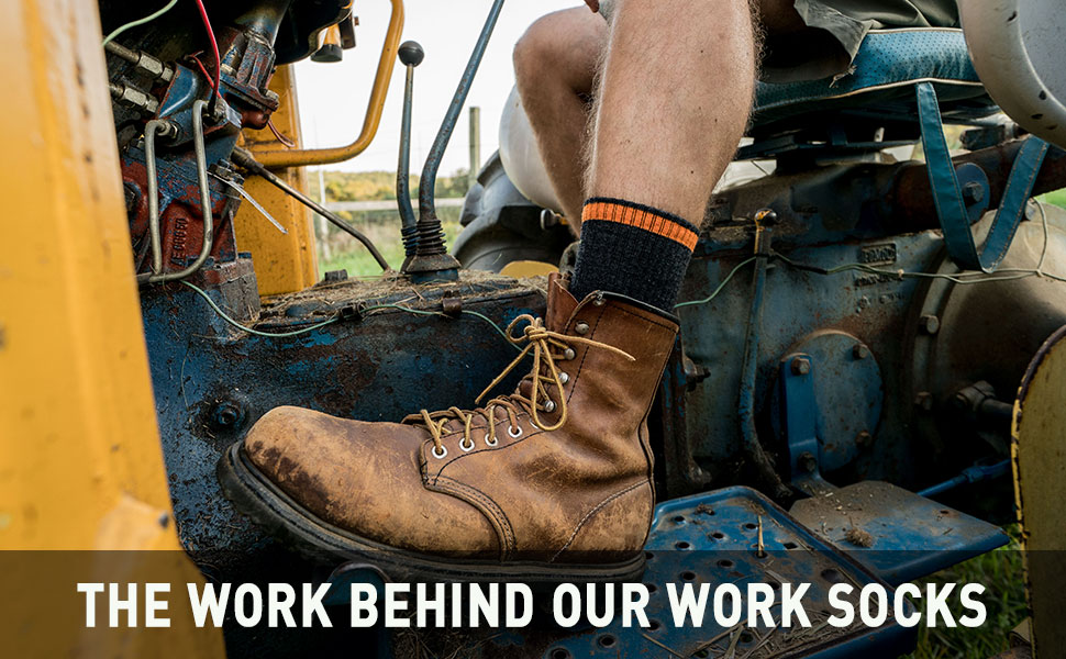 Worker on tractor wearing Darn Tough work sock