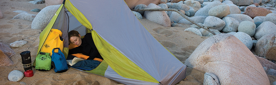 Woman reading in tent with Sea To Summit dry bags.