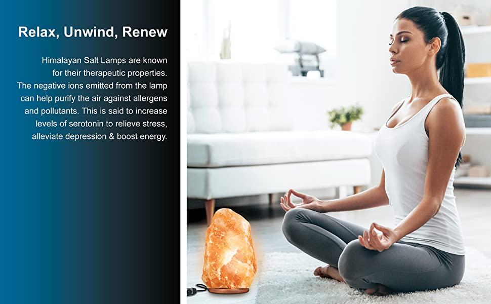 Woman practicing yoga with salt lamp in front of her.