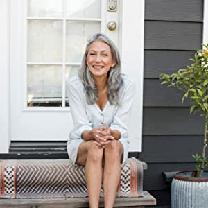 Happy middle-aged woman sits on her door step