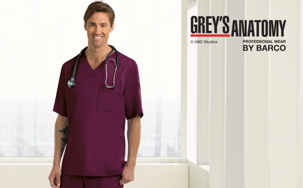 Male nurse standing in hallway wearing Barco Grey's Anatomy scrubs