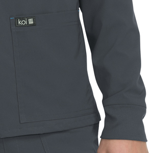 close up of koi Basics 448 men's scrub jacket featuring front pocket with logo detail and rib cuffs
