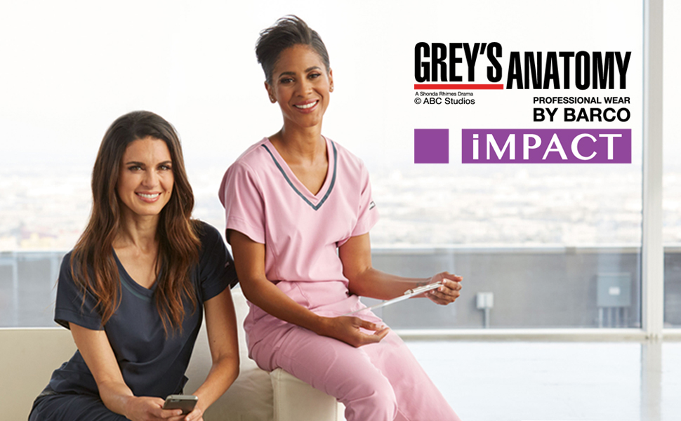 Two nurses sitting on a couch wearing Barco Grey's Anatomy Impact Scrubs