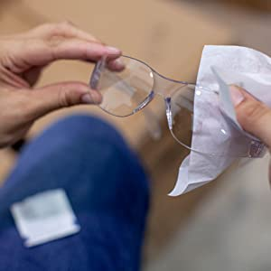 Image of clear lens safety glasses being wiped with a lens wipe.