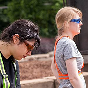 Image of women wearing colored safety glasses while working outdoors.