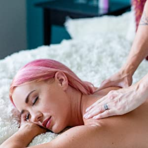 Woman with pink hair relaxing on white bed with two hands on her back as if getting a massage.