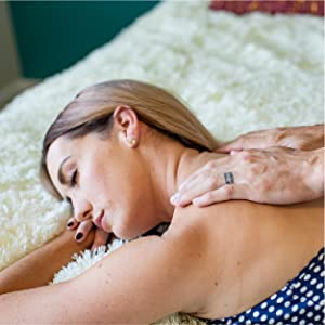 Woman lying in a relaxed position on soft, white blanket with eyes closed while being massaged