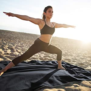 Girl doing yoga on waterproof outdoor blanket on the beach, sandproof weatherproof for outdoor use