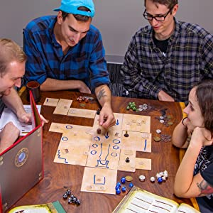 Friends play tabletop RPG using a gridded surface, drawn in dry-erase marker