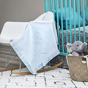 Blue baptism blanket in nursery on rocking chair next to crib