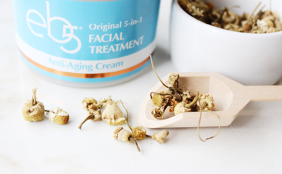eb5 facial cream with all natural ingredients, shown with comfrey root in a scoop