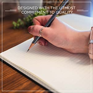 """Hand holding Blackwing pencil by a journal, words """"Designed with the utmost commitment to quality"""""""