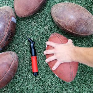 A hand gripping a football next to a ball pump
